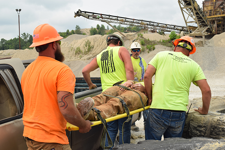 Plant workers carry man on stretcher
