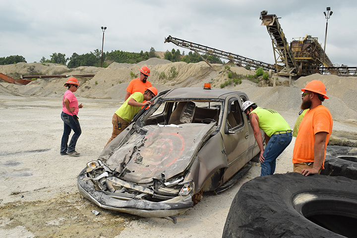 Plant workers inspect damage to pickup truck.